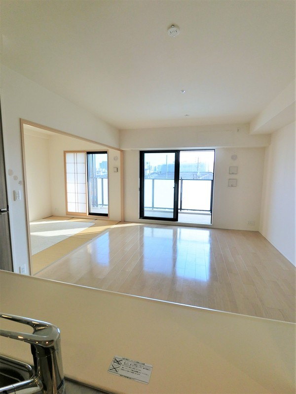 キッチンからバルコニーに向けて撮影。吊戸棚や垂れ壁がないので、キッチンとリビングの一体感があります。