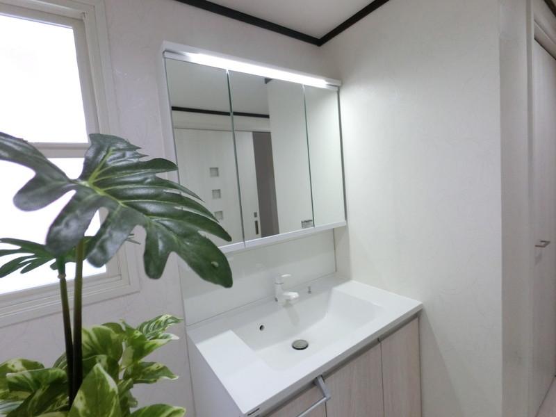 1階洗面所。収納豊富な化粧台。クローゼット収納にはコートを掛けて