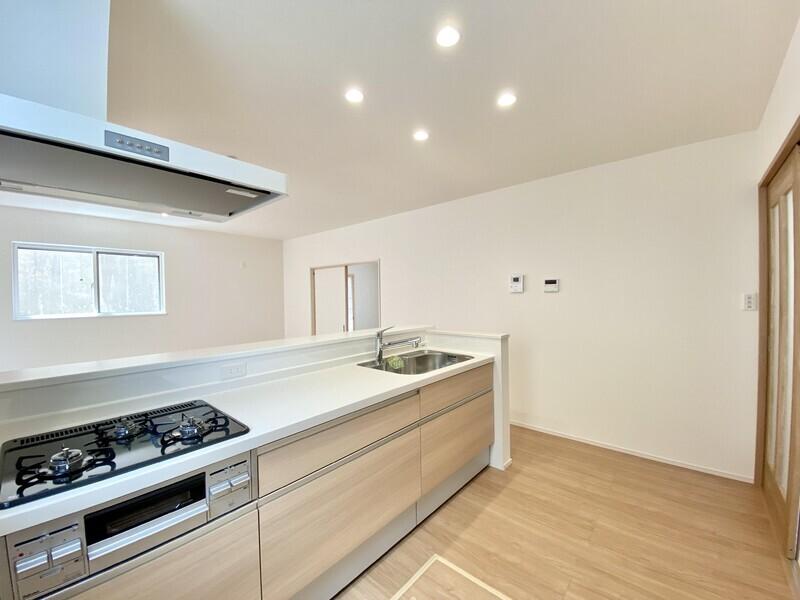 【キッチン】白壁や明るい床面と相性の良いウッディなシステムキッチンを採用♪冷蔵庫を置いても十分余裕のあるスペースを確保しています♪