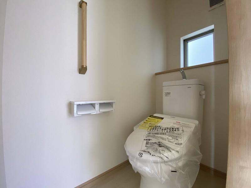 【1階トイレ】明るい色調でまとめたシンプルなトイレ。落ち着ける空間になっています。快適な温水洗浄便座付き。